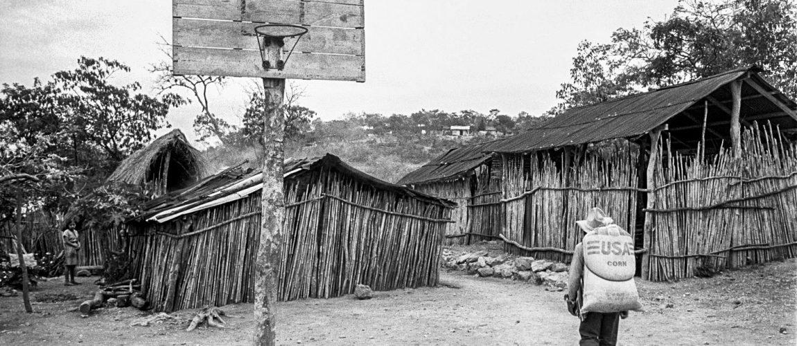Un hombre cruza la cancha de baloncesto del campamento con un saco de maíz en la espalda. La Cieneguita.1991.