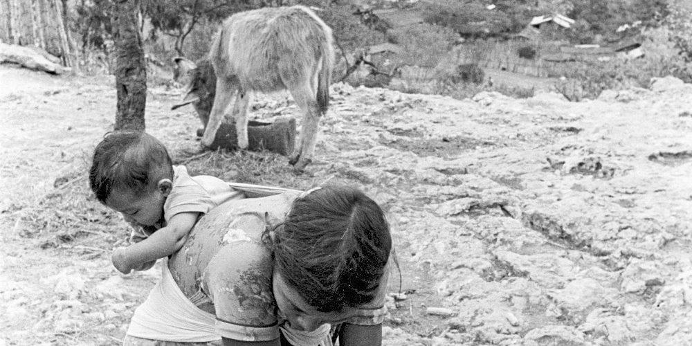 Una mujer con un bebé a la espalda lava una manta fuera de su casa. La Cieneguita. 1991