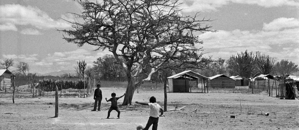 Muchachos jugando al fútbol en un área abierta del campamento. Nueva Libertad (El Colorado) 1992