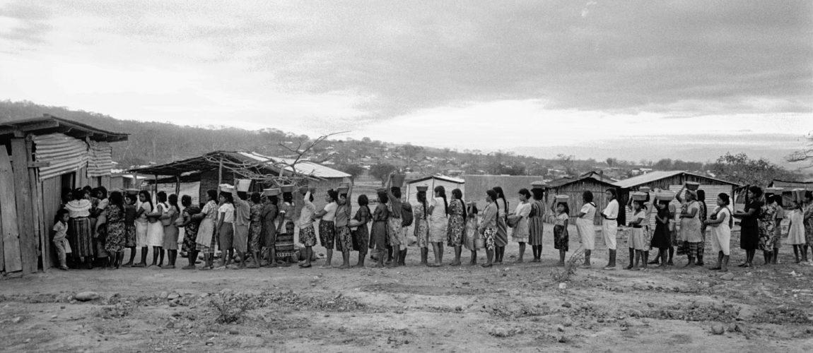 Las mujeres hacen fila para moler maíz en el molino comunitario. Nueva Libertad (El Colorado) 1992