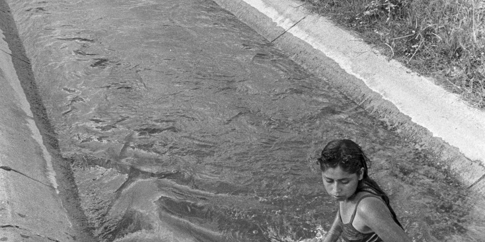 Una joven se baña y lava los platos en el canal de riego, la única fuente de agua del campamento. Nueva Libertad (El Colorado)1991