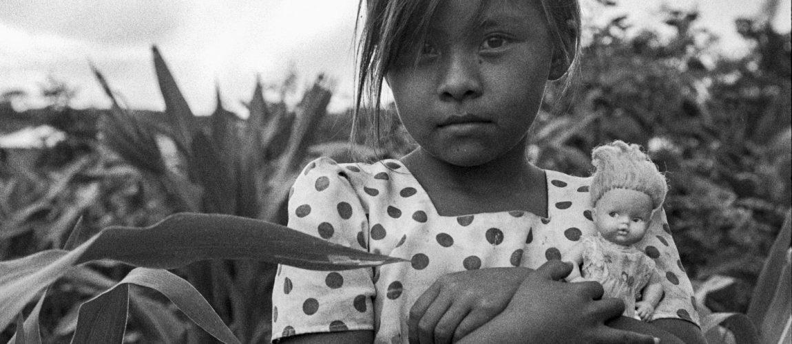 Niña con su muñeca en un campo de maíz del campamento. Nueva Libertad (El Colorado) 1993