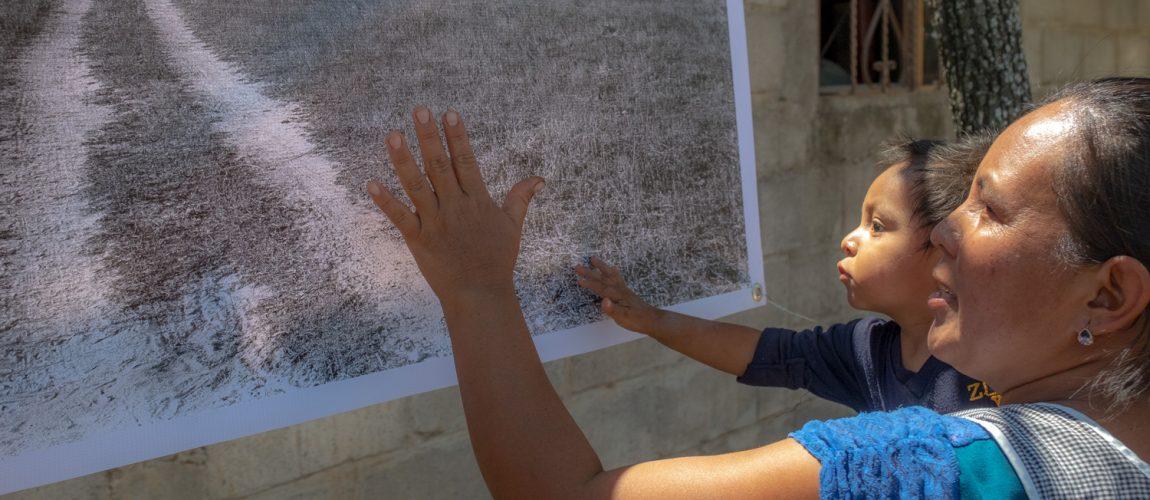 Una mujer y su hija tocan una foto del área original antes de la construcción de las casas en el campamento. Nueva Libertad (El Colorado) 2020