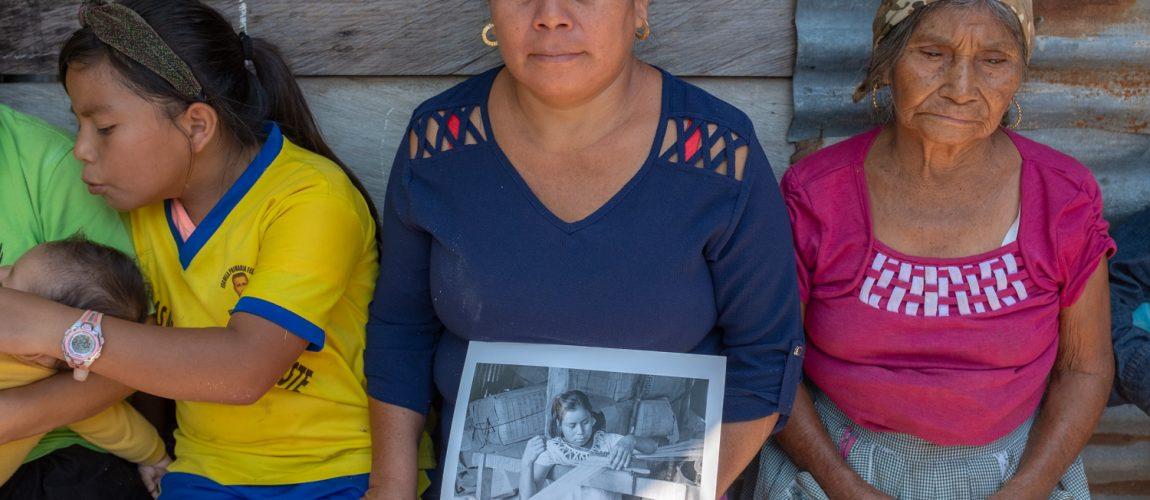 Eulalia Pedro Pascual sostiene una foto de ella hecha hace casi 30 años en el campamento Nueva Libertad cuando tenía 16 años. Está rodeada de varios miembros de la familia. Nueva Libertad (El Colorado) 2020