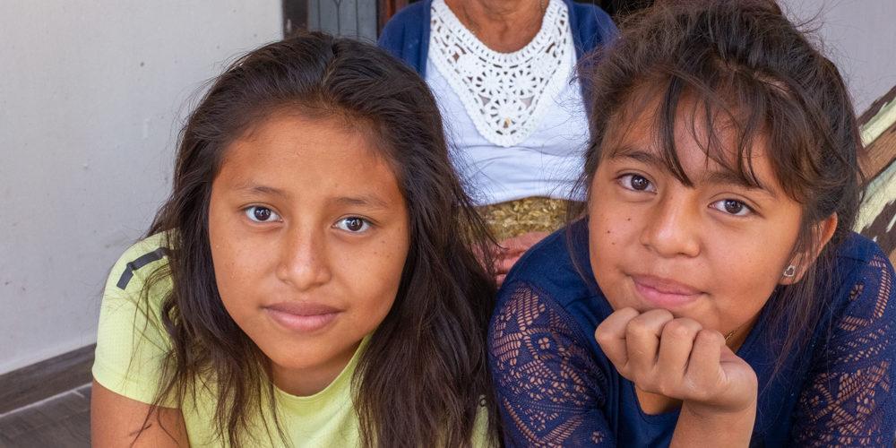 Juana Pascual Juan, de 66 años, posa en el porche de su casa en Nueva Libertad con dos de sus nietas: con la camiseta amarilla está Karen Nayeli Pedro José, de 12 y del lado derecho con el cabello recogido está Paola Pedro José, de 11. Nueva Libertad (El Colorado) 2020